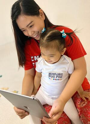 An English for Fun mom and her daughter proudly wear their uniforms to virtual preschool to see their friends.