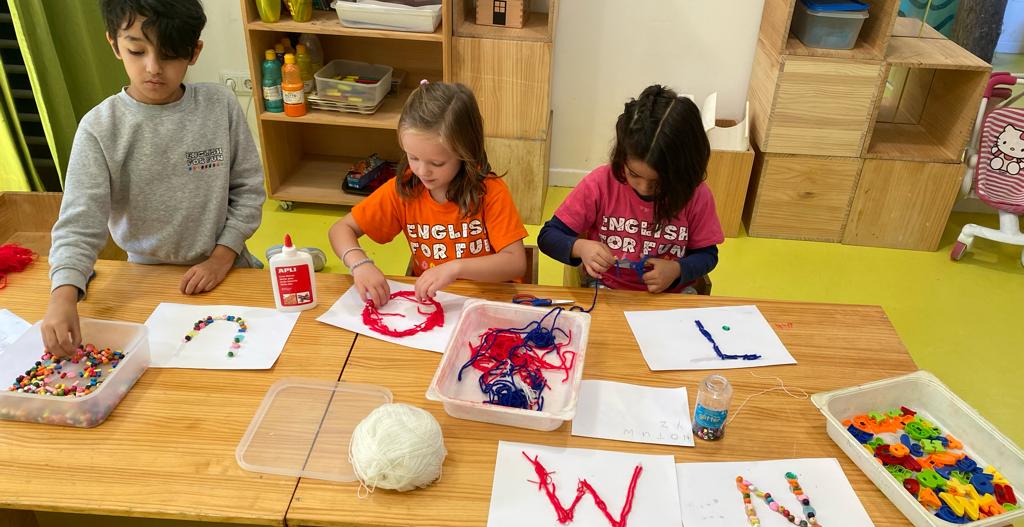 niños haciendo manualidades con letras